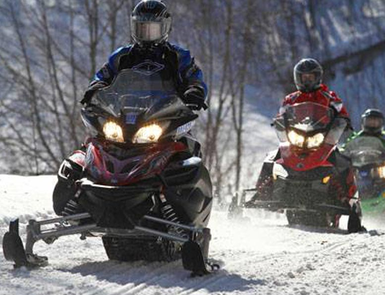 line-of-snowmobiles-on-trail